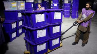 Un employé de la Commission électorale déplace des urnes et du matériel de vote dans un entrepôt à Kaboul, le 18 octobre 2018.