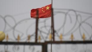 The Chinese flag flies behind razor wire at a housing compound in Yangisar, south of Kashgar, in China's western Xinjiang region -- at least 435 Uighur intellectuals have been imprisoned or forcibly disappeared in the area since April 2017