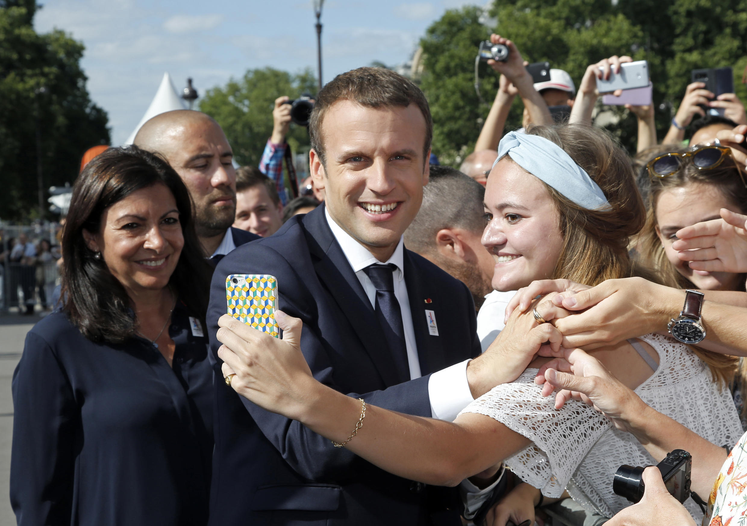 French President Emmanuel Macron (C) poses for a 'selfie' with Paris Mayor Anne Hidalgo (L) during a visit to a site on the Pont Alexandre III in Paris on June 24, 2017.