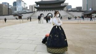 Una mujer con un traje tradicional 'hanbok' visita el palacio Gyeongbokgung de Seúl protegida con una mascarilla el 30 de enero de 2020