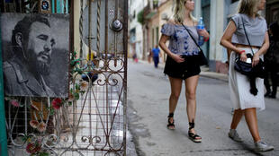 Turistas passam em frente a foto de Fidel, no centro de Havana