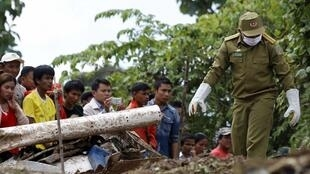 Villagers watch rescue personnel at the crash site of an ATR-72 turboprop plane near Pakse