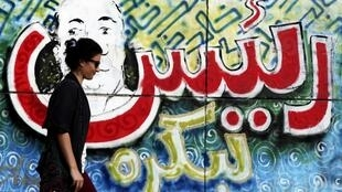 "A woman walks in front of a wall with graffiti reading ""President for tomorrow"" near Tahrir Square in Cairo, 18 June, 2012"