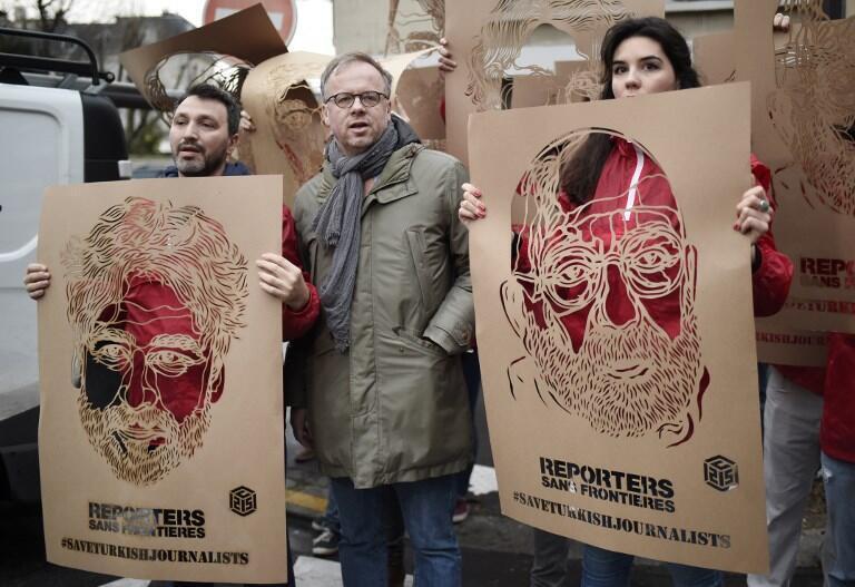 Des membres de RSF brandissent des portraits de journalistes turcs emprisonnés dans leur pays, le 5 janvier 2018, devant l'ambassade de Turquie à Paris.