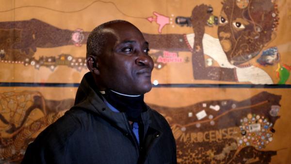 Mega Mingiedi, artiste-plasticien du collectif Eza Possibles et coordinateur du projet « Kinshasa Chroniques » à Kinshasa, devant son diptyque « Kinshasa I et Kinshasa II ».