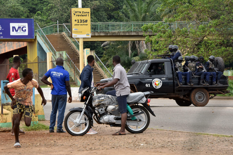 Civiles observan un vehículo policial en el barrio de Kalum, Conakry, el 5 de septiembre de 2021