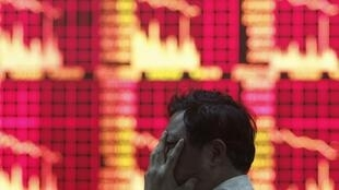 A man in front of an electronic screen at a brokerage house in Shanghai