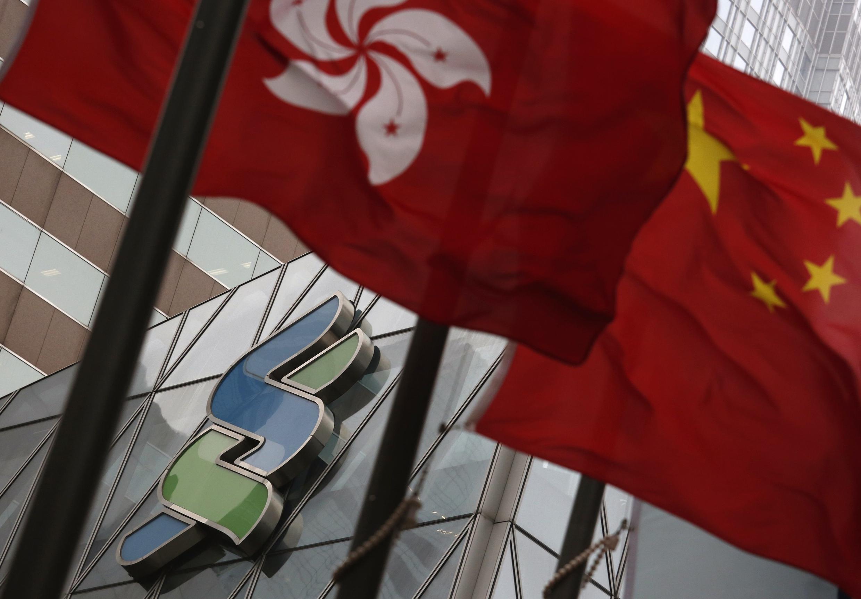 资料图片,香港街头特区政府旗帜与中国国旗。摄于2015年3月
