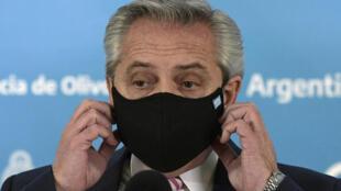 El presidente de Argentina, Alberto Fernández, se quita la máscara facial durante una conferencia de prensa en la residencia presidencial de Olivos, en Buenos Aires, el 12 de agosto de 2020