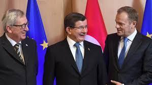 O primeiro-ministro turco, Ahmet Davotuglu, entre o presidente do Conselho Europeu, Donald Tusk (à dir.), e o presidente da Comissão Europeia, Jean-Claude Juncker.