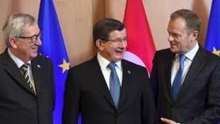 O Primeiro - ministro turco, Ahmet Davutoglu, acolhido em Bruxelas pelo Presidente da Comissão Europeia, Jean-Claude Juncker (à esquerda) e o Presidente do Conselho Europeu,  Donald Tusk ( à direita)