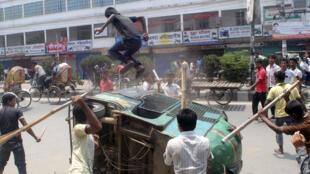 Des travailleurs du textile à Dacca, lors d'une manifestation réclamant l'arrestation du propriétaire de l'immeuble dont l'effondrement a causé la mort de plus de 300 personnes, mercredi.