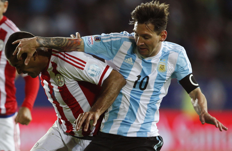 Mchezaji wa Argentina Lionel Messi akiwania mpira na mchezaji wa Paraguay, Paulo da Silva.