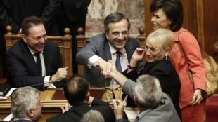 Algunos diputados felicitan al primer ministro griego, Antonis Samaras (centro) y al ministro de finanzas, Yannis Stournaras (izquierda), después de la votación de las reformas, el 18 de julio de 2013.