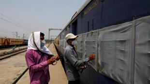 Des travailleurs réparent des moustiquaires d'un train de voyageurs stationné qui sera équipé pour soigner les patients atteints du coronavirus, dans une gare de triage à New Delhi, en Inde, le 15 juin 2020.