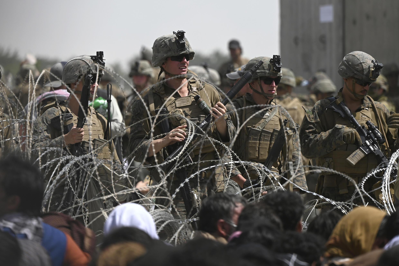 Soldados estadounidenses vigilan atrás de alambres de púas mientras afganos esperan en las cercanías del aeropuerto de Kabul, el 20 de agosto de 2021