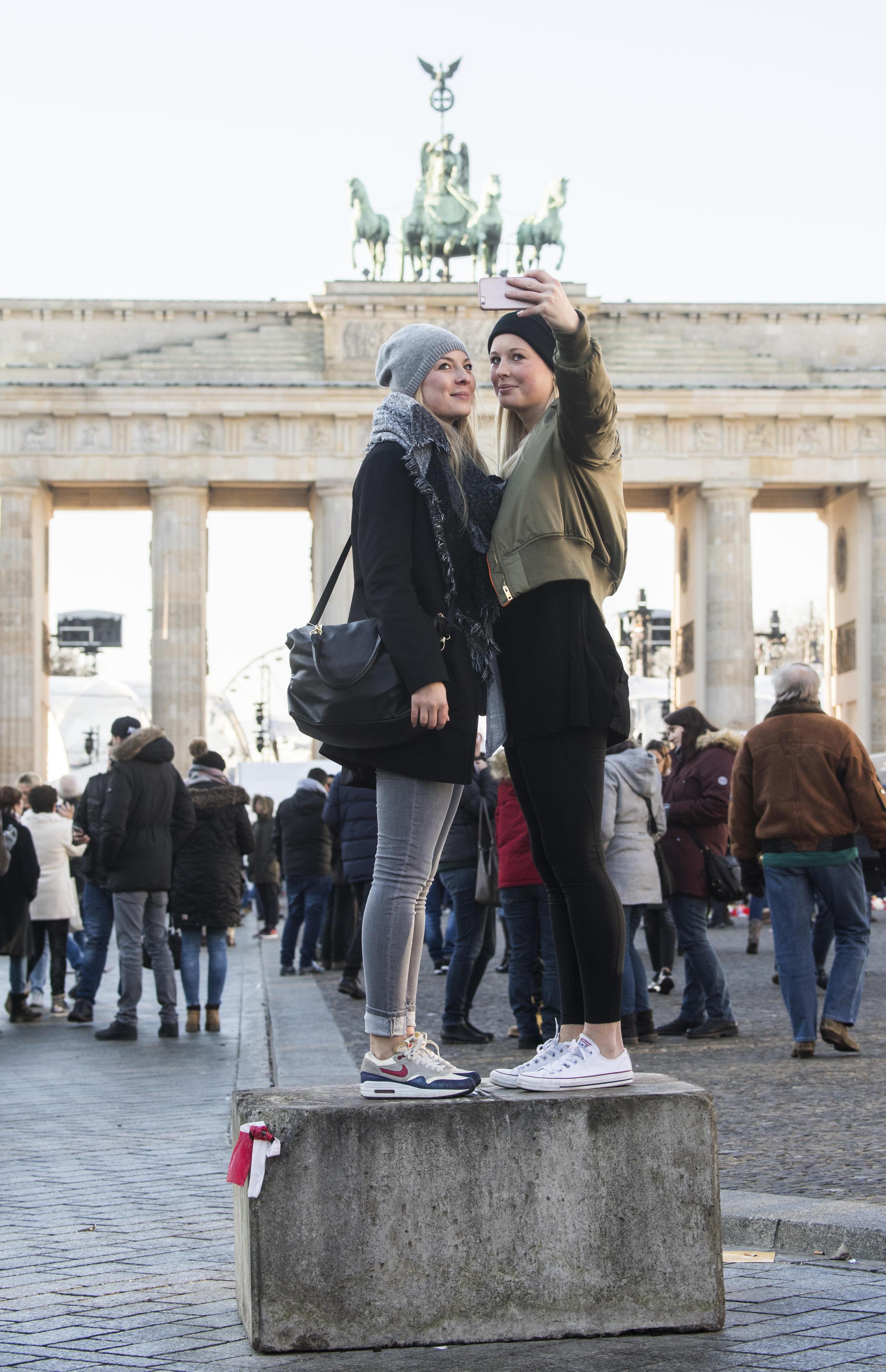 Du khách chụp ảnh kỷ niệm trước cổng Brandenburg, Đức vào ngày cuối năm 2016.