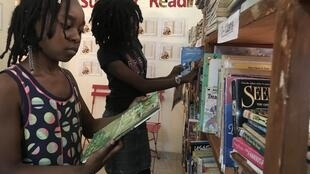 Fatiha and her sister looking at books at Chez Alpha.