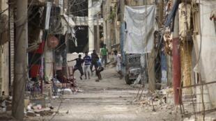 Soldados da rebelião síria jogam futebol em meio aos escombros na cidade de Deir al-Zor , no leste da Síria.
