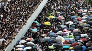Акция протеста в центре Гонконга 12 июня. После мирных демонстраций 2014 года зонтик стал символом протеста в городе.