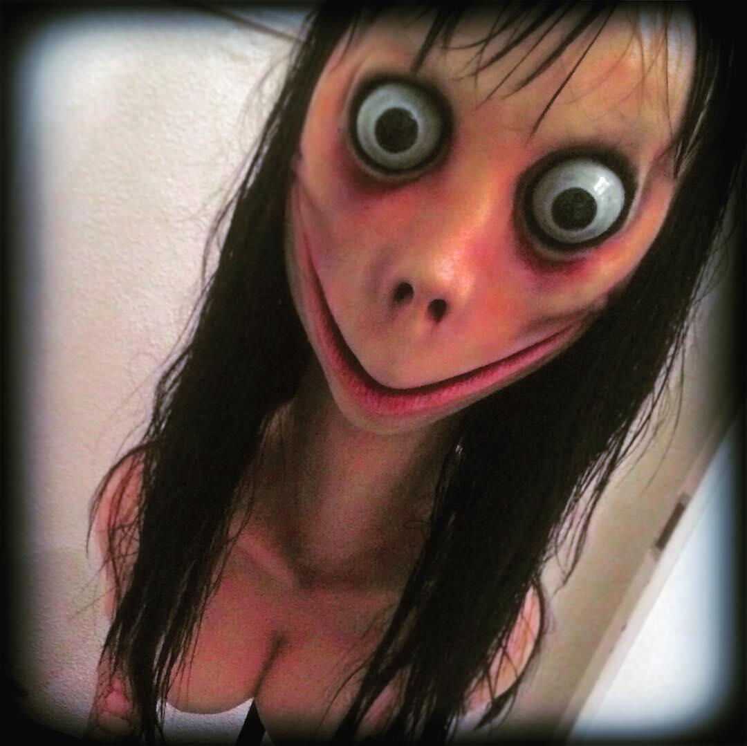 Momo es una mujer de cara distorsionada, con ojos saltones y una sonrisa grande e inquietante.