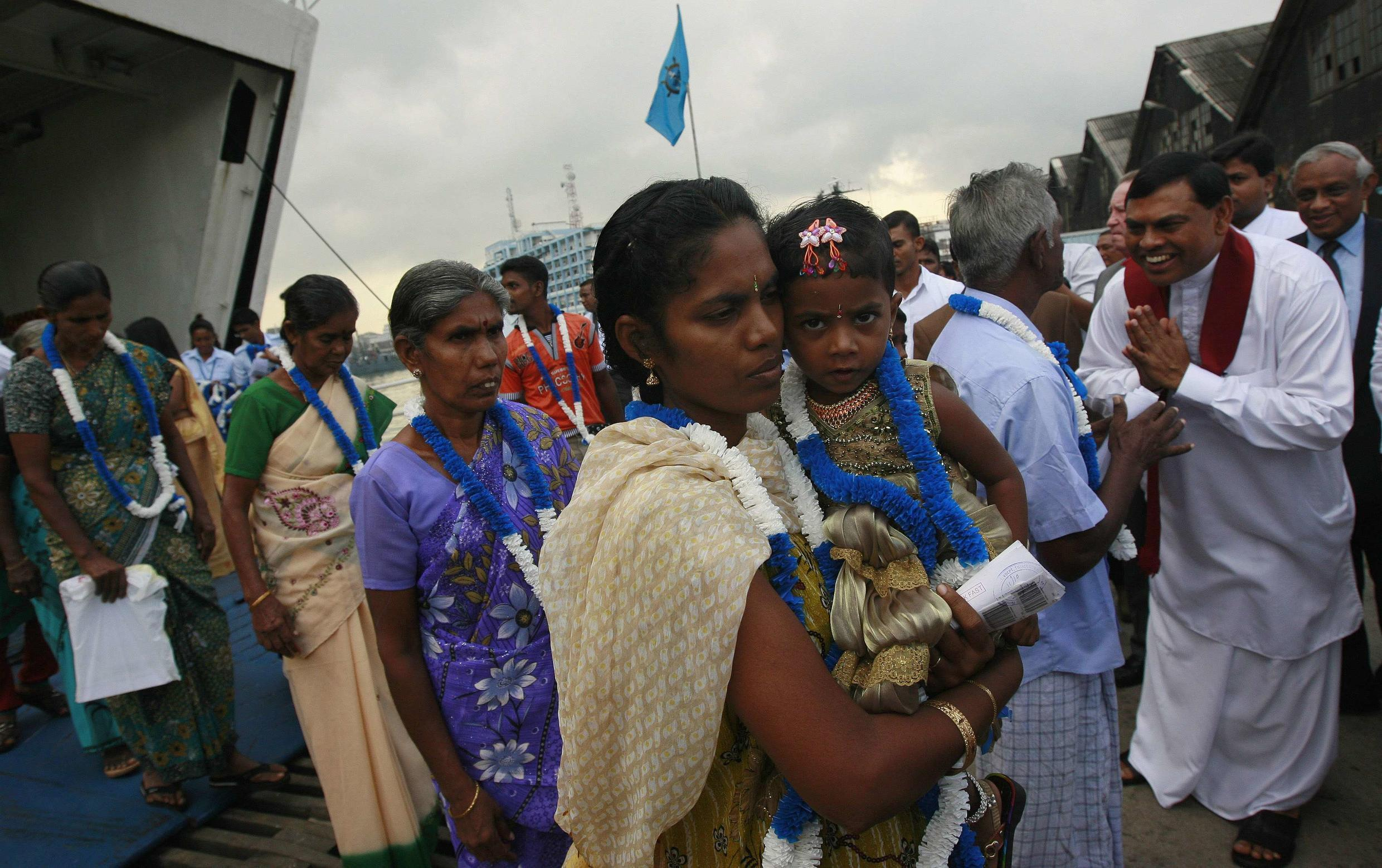 An ethnic minority Tamil woman arrives with her daughter to go to her native village