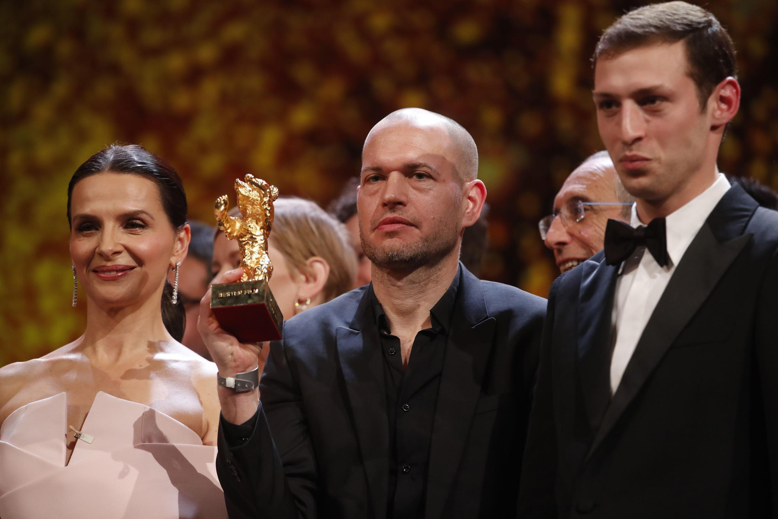 Director Nadav Lapid (c) with the Berlinale Golden Bear flanked by jury president, French actress, Juliette Binoche (l) and Synonymes' leading actor, Tom Mercier (r), 17 February 2019