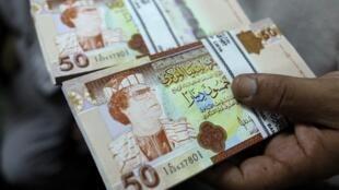 Des dinars libyens à l'effigie de Mouamar Khadafi en 2011 à la Banque centrale de Tripoli.