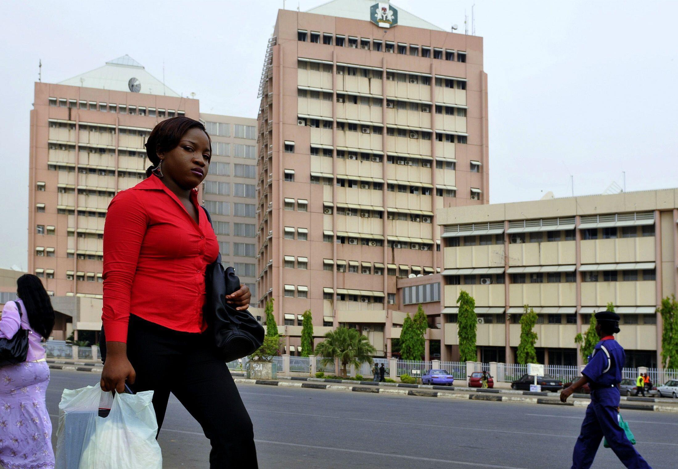 A woman walks past the federal secretariat  in Abuja