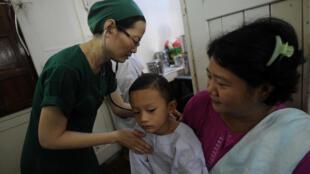 Un médecin s'occupe d'un enfant à l'Hôpital musulman gratuit.