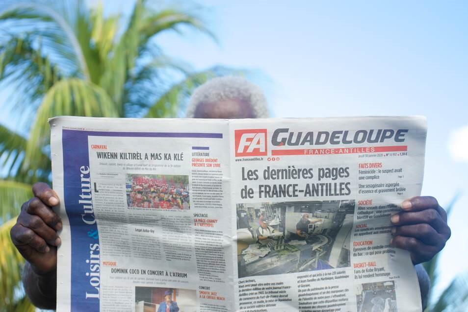 Un homme lit un exemplaire du quotidien régional France Antilles, le 30 janvier 2020, à Pointe-à-Pitre, en Guadeloupe.