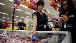 Un miembro de la Agencia de Vigilancia Sanitaria mide la temperatura de la nevera donde está la carne en un supermercado antes de analizarla en su laboratorio, este 20 de marzo de 2017 en Río de Janeiro.