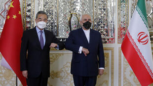 Iranian Foreign Minister Mohammad Javad Zarif greets his Chinese counterpart Wang Yi ahead of the signing of a 25-year cooperation pact between the US rivals