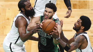 Boston Celtic's Jayson Tatum, centre, drives between Brooklyn players James Harden, left, and Kyrie Irving