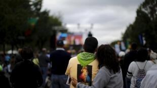 Un couple devant un écran géant retransmettant une célébration du pape à Philadelphie, le 27 septembre 2015.