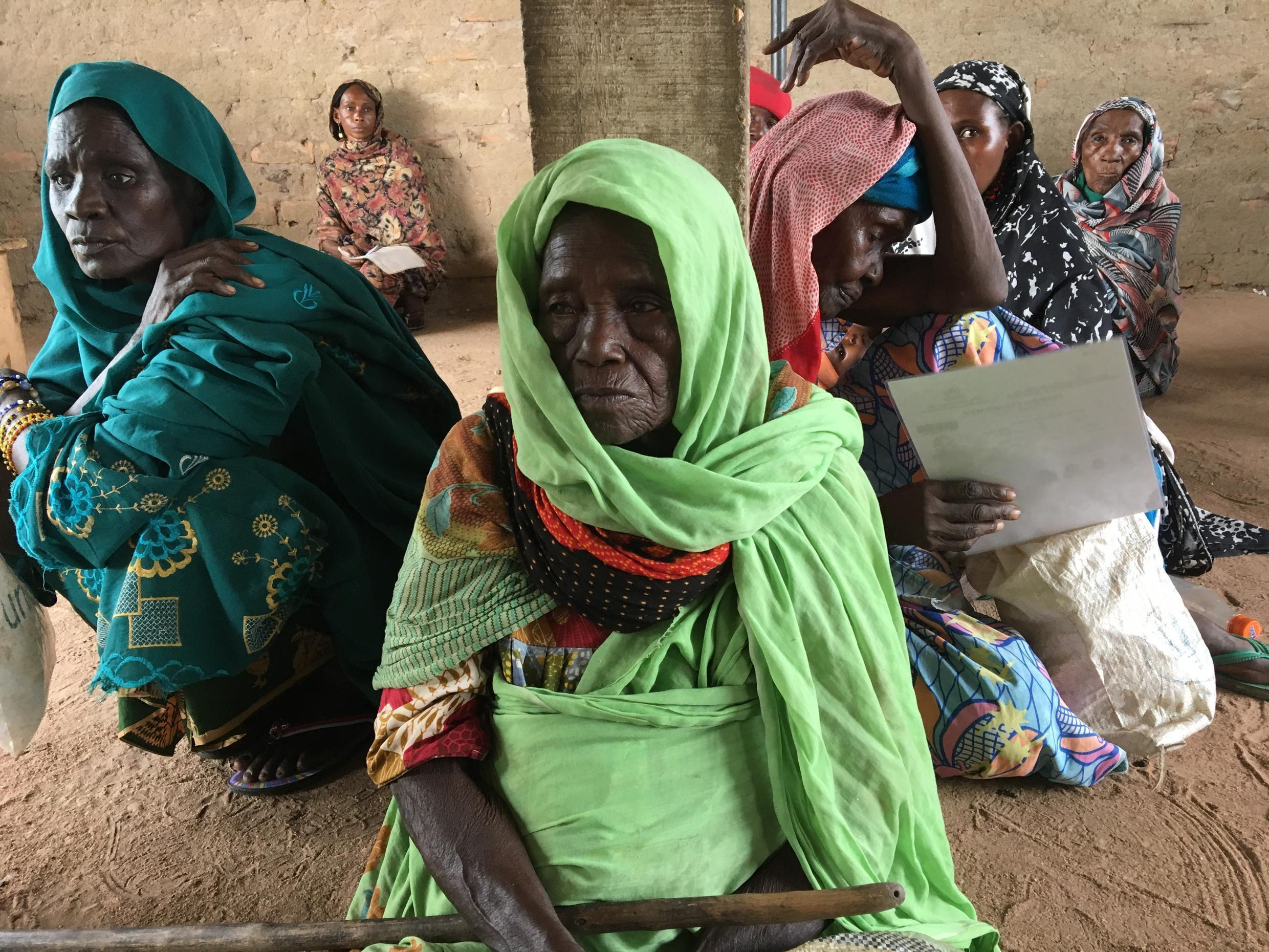 Halima Mahabas (centre), 80, originally from Pawa, CAR, waiting for her 3000XFA stipend from the World Food Program