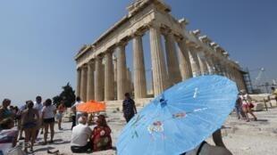 Turistas se protegem do calor na Acrópole, em Atenas.
