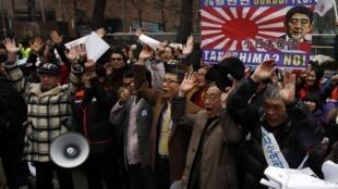 2013年2月22日,一些韩国活动人士在首尔日本驻韩国大使馆门前集会,抗议日本地方政府在两国有主权争议岛屿问题上的立场。