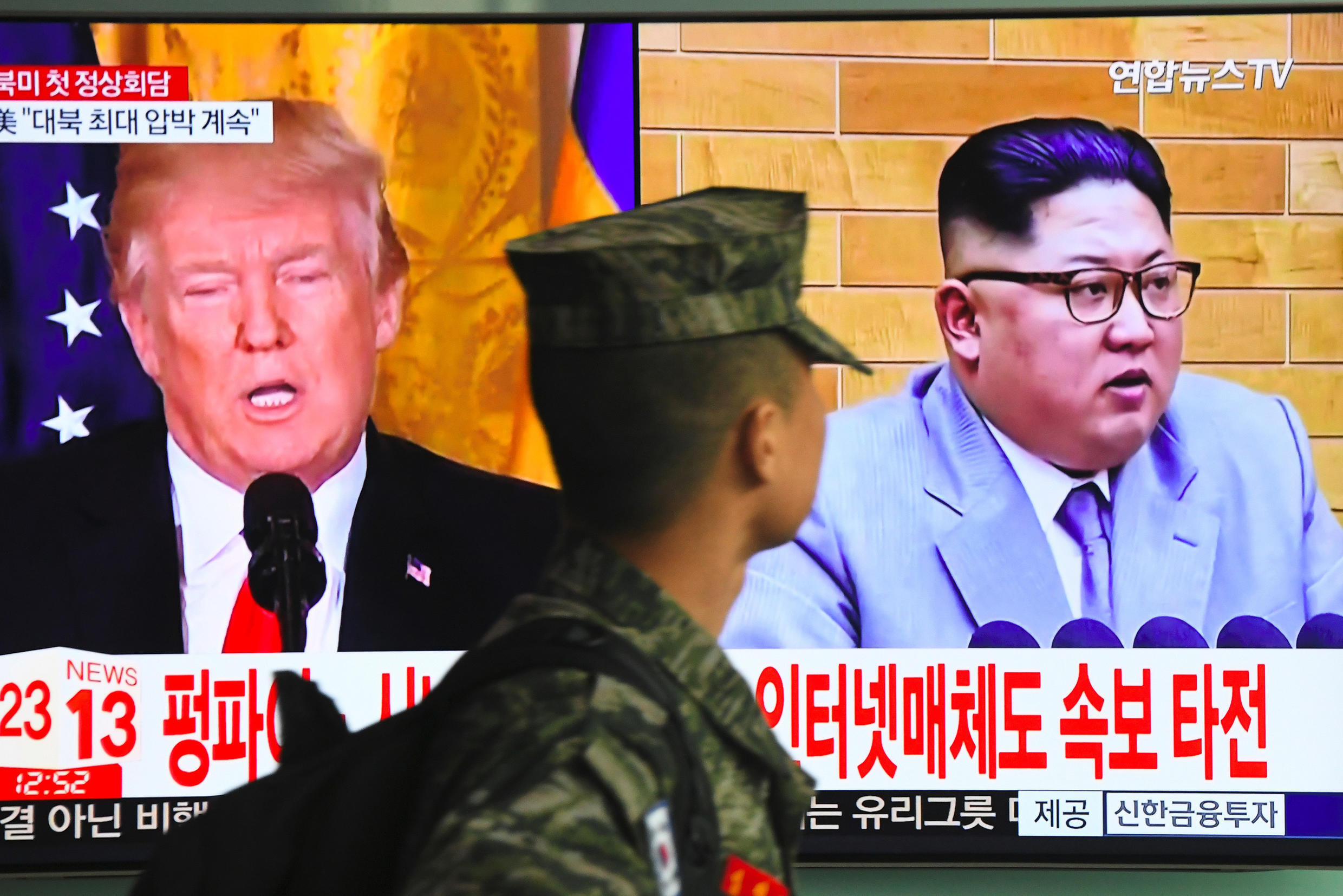 A South Korean soldier walks past a television screen showing pictures of US President Donald Trump (L) and North Korean leader Kim Jong Un at a railway station in Seoul on March 9, 2018. U