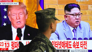 A South Korean soldier walks past a TV screen showing pictures of US President Donald Trump (L) and North Korean leader Kim Jong-un