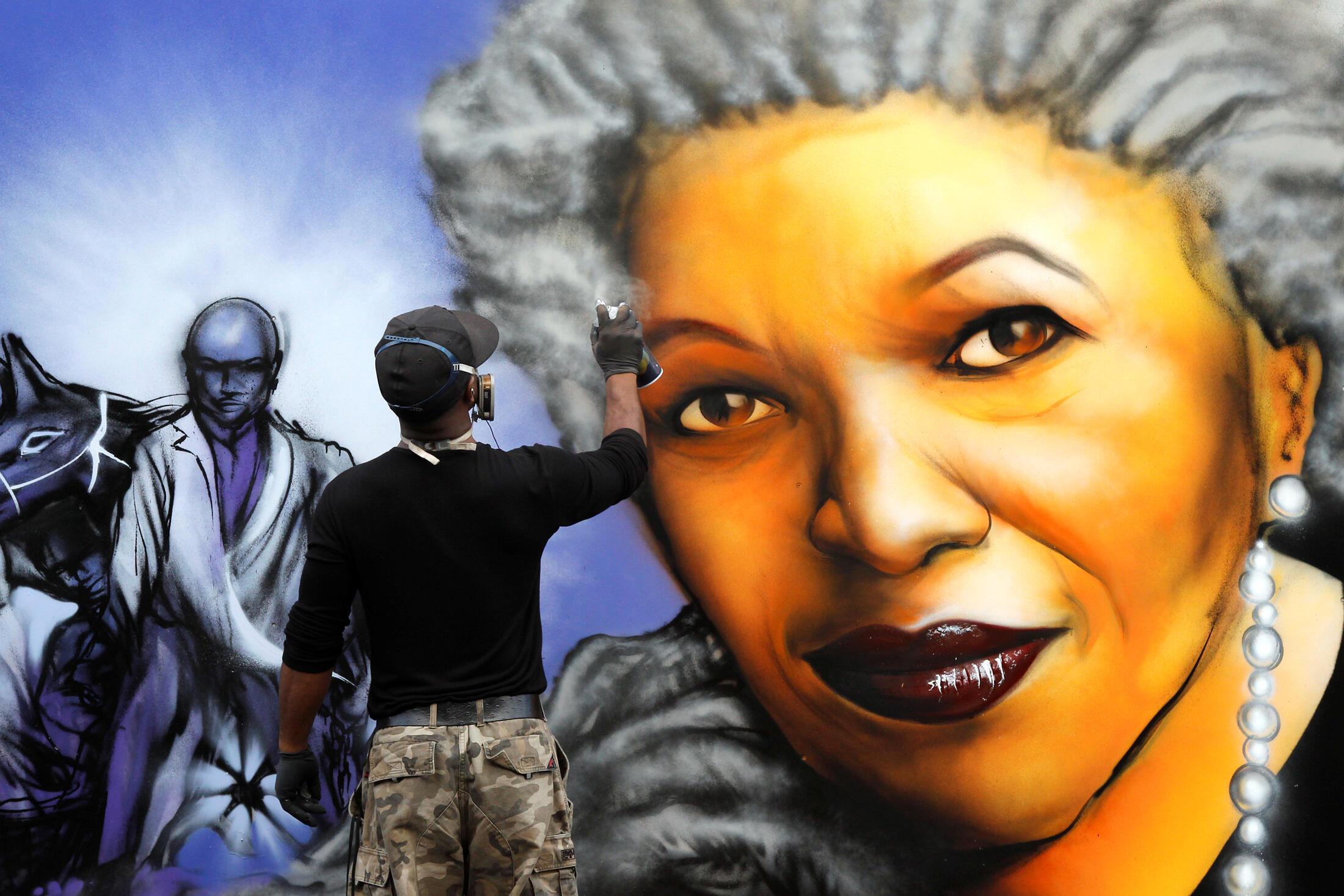 یک هنرمند در حال نقاشی تصویری از موریسون روی دیوار - پاریس 2010