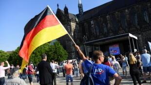 Un partisan de l'AfD brandit un drapeau national allemand avant le dernier meeting du parti d'extrême droite pour les régionales dans le Land de Saxe-Anhalt Magdebourg, le 4 juin 2021.