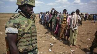 Un soldat ougandais de l'Amisom surveille des membres des shebabs, après leur reddition à Garsale, le 22 Septembre 2012.