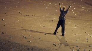 Cercado de pedras por todos os lados, manifestante pró-Mursi sinaliza para rivais no Cairo