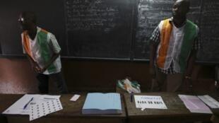Des agents des bureaux de vote, vêtus aux couleurs de la Côte d'Ivoire, attendent les électeurs, à Abidjan, le 11 décembre 2011.