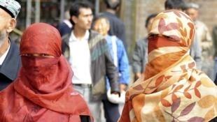Mujeres uigur en velo en la provincia de Xinjiang.