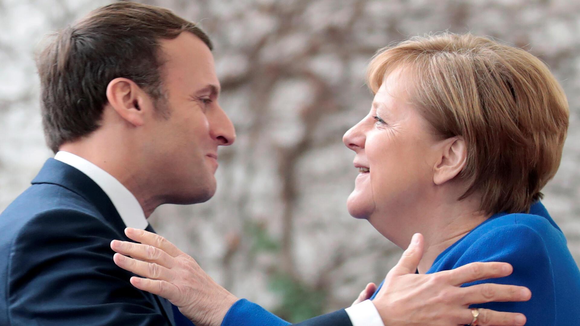Le président français Emmanuel Macron accueilli par la chancelière allemande Angela Merkel, lors du sommet sur la Libye, à Berlin, le 19 janvier 2020.