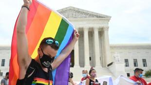 Un hombre ondea una bandera con los colores del arco iris frente a la Corte Suprema de Estados Unidos, que publicó una decisión que dice que la ley federal protege a los trabajadores LGBTQ de la discriminación, el 15 de junio de 2020 en Washington