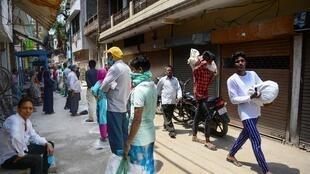 People wait in line to collect free rations from a government store during India's nationwide lockdown