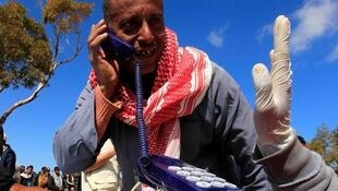 An Egyptian man who fled the unrest in Libya talks on a phone provided by Telecom Without Borders on the Tunisia/Libya border.